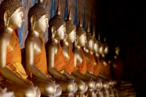 Golden buddha statues inside a Thai temple.