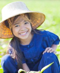 Thai girl smiling in front of rice field.